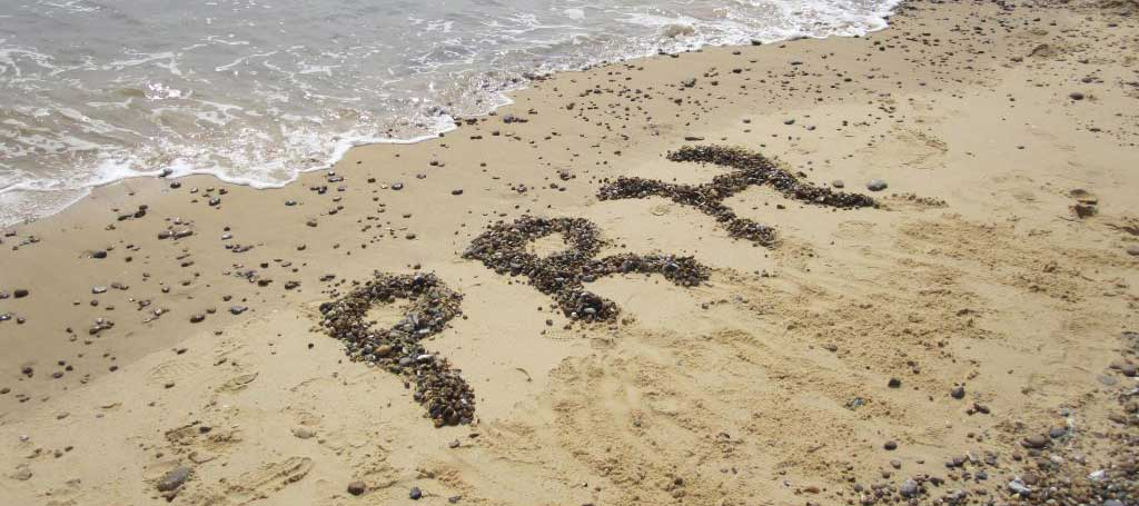 PRH written with pebbles on a beach